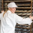 Baker pushing rack full of bread into the oven — Stockfoto