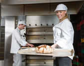 Baker with tasty loaf of bread on a peel — Stock Photo