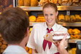 Saleswoman in baker's shop selling bread to customer — Stockfoto