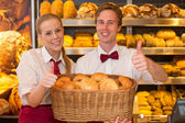 Bakers in bakery with basket full of bread — Stock Photo
