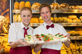 Two bakers holding tray with sandwiches in bakery — Stock Photo