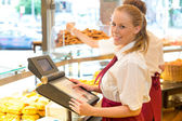 Cashier in baker's shop posing with cash register — Stock Photo