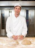 Smiling baker kneading dough in bakery — Stock Photo