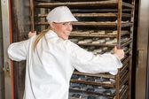 Baker pushing rack full of bread into the oven — Stock Photo
