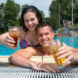 Couple with drinks in the sund at pool — Stock Photo