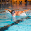 Man swims butterfly style in public swimming pool — Stock Photo #30562621