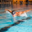 Man swims butterfly style in public swimming pool — Stock Photo