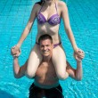 Girl sitting on man's shoulders at swimming pool — Stock Photo