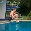 Man having fun jumping from diving board at swimming pool — Stock Photo