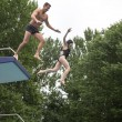 Couple jumping from a diving board into a swimming pool — Stock fotografie