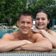 Couple enjoying holidays at pool edge — Stock Photo