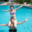 Girl sitting on man's shoulders at swimming pool — Foto de Stock