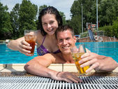 Couple with drinks in the sund at pool — Zdjęcie stockowe