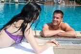 Man and woman flirting at swimming pool — Stock Photo