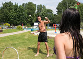 Couple playing badminton at swimming poot or park — Stok fotoğraf