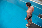 Man standing on diving board at public swimming pool — 图库照片