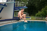 Man having fun jumping from diving board at swimming pool — Stok fotoğraf