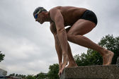 Swimmer standing on starting block at swimming pool — Stock Photo