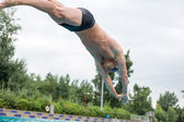 Man ready to jump on staring block at swimming pool — Foto de Stock