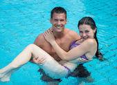 スイミング プールで運ぶ女の子を男します。. — ストック写真