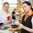 Client at shop paying at cash register — Stock Photo #41025737