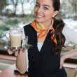 Waitress posing with cup of coffee in cafe or restaurant — Stock Photo