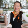 Waitress posing with cup of coffee in cafe or restaurant — Stock Photo #41026207