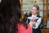 Waitress gives piece of cake to client — Stock Photo