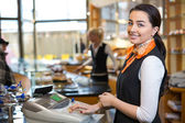 Shopkeeper and saleswoman at cash register or cash desk — ストック写真