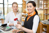 Client at shop paying at cash register — Stock Photo
