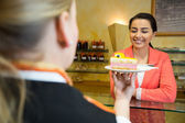 Waitress serving cake to customer in cafe — Stock Photo