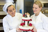 Confectioners or bakers presenting wedding cake — Stock Photo