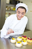 Confectioner preparing cakes at bakery or confectionery — Stock Photo