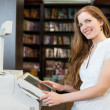 Cashier at cash register in bookstore — Stock Photo #43427571