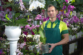 Florist posing in flower shop with orchid — Stock Photo