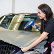 Car wrappers using heat gun to flatten vinyl film — Stock Photo