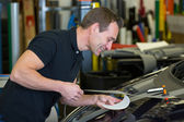 Worker in car wrapping workshop glues foil to car — Stock Photo