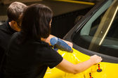 Car wrappers using heat gun to prepare vinyl foil — Stock Photo