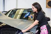 Car wrappers using heat gun to flatten vinyl film — Stock Photo