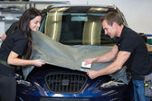 Car wrappers using squeegee to straighten vinyl film — Stock Photo