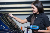 Car wrapper using heat gun and squegee for tinting window — Stock Photo