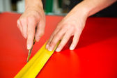 Car wrapping specialist cutting foils with box cutter — Stock Photo