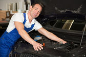 Mechanic in garage repairing car — Stock Photo