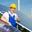 Photovoltaic engineer showing thumbs up at solar panel array — Stock Photo #47750895