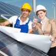 Photovoltaic engineers with construction plan at solar panels — Stock Photo #47750943