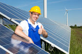 Photovoltaic engineer showing thumbs up at solar panel array — Stock Photo