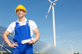 Engineer posing with wind turbine and solar panels — Stock Photo