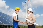 Engineers shake hands in front of solar panels and wind turbine — Stock Photo