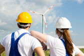 Engineers or installers looking at wind energy turbine — Stock Photo