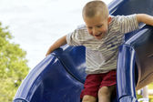 Young Boy Sliding At Schoolyard Playground — Stock Photo